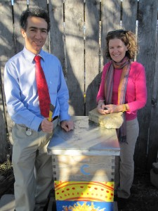 Alex Kachen and I stand behind a bee hive.